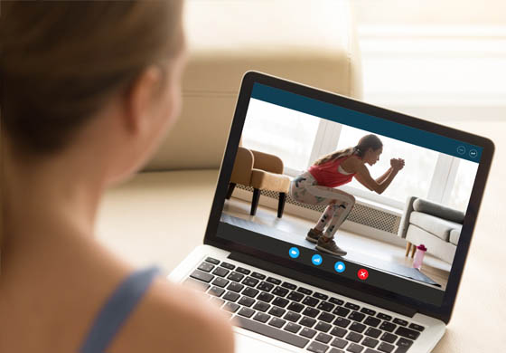 Woman watching workout on laptop