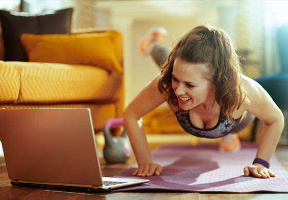 Woman doing a workout watching her laptop