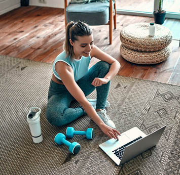 Woman sitting with laptop and workout gear