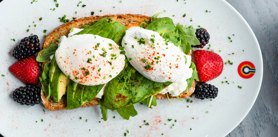 Avocado toast with poached eggs and a side of fresh berries