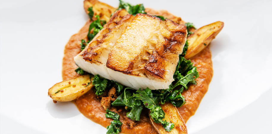 Fish on a bed of kale and sauce, with potatoes