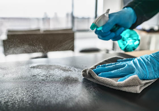 hands cleaning a surface with disinfectant